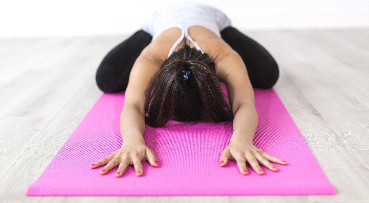 ragazza in una posizione di yoga sopra il suo tappetino